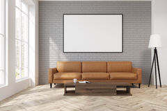 Gray living room with a beige sofa, poster, lamp. Gray living room interior with a beige sofa standing near a wooden coffee table with a book on it. There is a Royalty Free Stock Photo