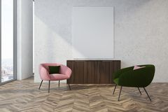 Gray living room, pink and green armchairs. Modern living room interior with a wooden floor, concrete walls and a pink and green armchairs near a vertical poster Royalty Free Stock Photo
