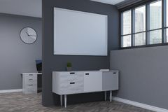 Gray living room, poster, chest of drawers side. Minimalistic living room interior with a wooden floor, gray walls and a white and wooden chest of drawers with a Royalty Free Stock Images