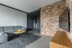Living room with brick wall. Gray living room with sofa, table, curved tv and industrial brick wall stock photos