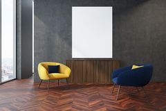 Gray living room, yellow and blue armchairs. Modern living room interior with a wooden floor, gray walls and a yellow and blue armchairs near a vertical poster Royalty Free Stock Image