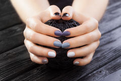 Gray manicure with black ball of yarn Royalty Free Stock Photo