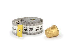 Gray measuring tape and thimble on white. Gray measuring tape and thimble, isolated on white background Stock Image