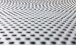 Gray metal background, round perforated metal texture. Reflections and blur. Stock Images