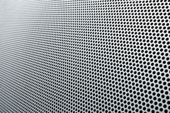 Gray metal background, round perforated metal texture with reflections Royalty Free Stock Photography
