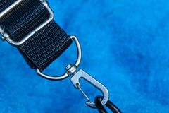 Gray metal carbine on a black harness on a blue background royalty free stock photo