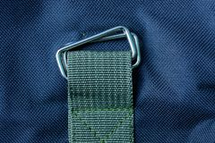 Gray metal carbine on a green harness sewn to the black fabric stock images