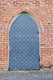 Gray metal door, red brick wall, pavement of gray stone Stock Photos