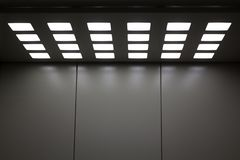Gray metal elevator with square lamps in the ceiling royalty free stock image