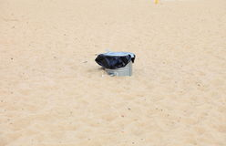 Gray metal garbage bin or can on beach Royalty Free Stock Images