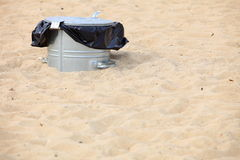 Gray metal garbage bin or can on beach Royalty Free Stock Photography