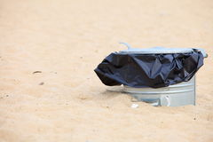 Gray metal garbage bin or can on beach. Gray metal garbage bin or trash can with a plastic bag inside beach outdoor Stock Photography
