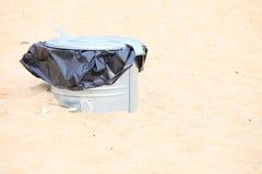 Gray metal garbage bin or can on beach. Gray metal garbage bin or trash can with a plastic bag inside beach outdoor Royalty Free Stock Photos