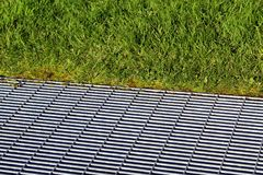 Metal grid on the ground in a green grass Royalty Free Stock Image