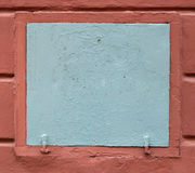 Gray metal hatch in red wall. Background Royalty Free Stock Image