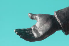 Gray Metal Statue Hand outstretched against turquoise blue background. The hand of a gray metal statue is reaching out in what looks like acceptance or a Royalty Free Stock Image