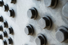Gray metal surface with hexagonal bolt heads Stock Image