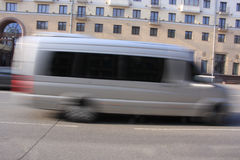 A gray minibus down with a blur in motion. The movement of a gray minibus down the street in the afternoon with a blur in motion stock images