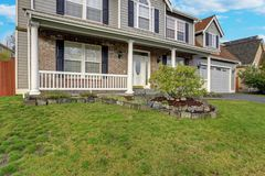 Gray mixed siding home with nice landscaping. Gray mixed siding home exterior with nice landscaping on a perfect sunny day stock photography
