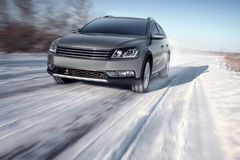 Gray modern car drive speed on road at winter daytime Stock Photography