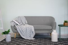 Gray modern couch with cushion and blanket and black carpet. Gray modern couch with pillow and blanket and black carpet stock images