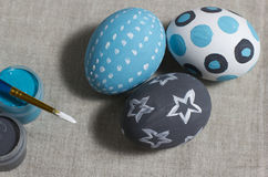 On a gray napkin three eggs and paints with a brush. For a holiday of Easter the ornamented three eggs lie on gray cotton fabric Royalty Free Stock Image
