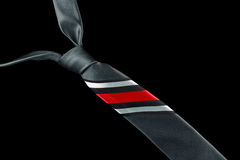 Gray necktie in silk with stripes. One necktie isolated against a black background. White, black and red stripes Stock Images