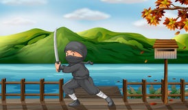 A gray ninja with a sharp sword near the wooden mailbox Stock Photos