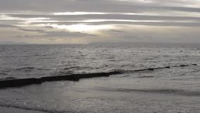 Gray ocean waves lapping against shore under a partially overcast afternoon sky. stock footage