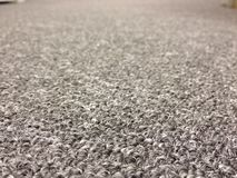 Gray office carpet with foreground in focus Royalty Free Stock Images