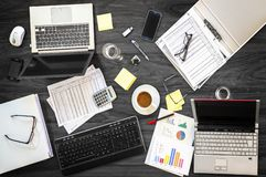 Gray office desk at a business meeting with laptops, phones and royalty free stock images