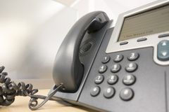 Gray office phone on desk. Grey office telephone land line royalty free stock photo