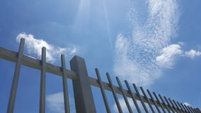 Gray painted metal fence with blue sky background Stock Photo