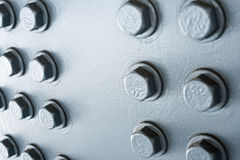 Gray painted metal surface with hexagonal bolt heads Royalty Free Stock Photos