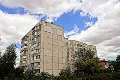 Gray panel apartment house against the sky in trees and green vegetation Stock Photos