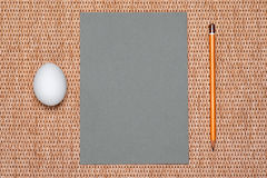Gray paper and pencil and egg on background Stock Images