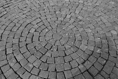 Gray Pavement of cobblestones laid in concentric circles royalty free stock photo