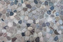 Gray pebble mosaic neutral background. Closeup of neutral colored gray paving stone. Abstract pebble mosaic patterned background stock image