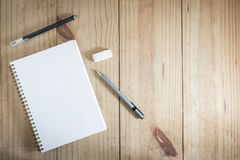 Top view of working object : gray pencil and black pen near white notebook on wooden table. Gray pencil and black pen near white notebook on wooden table Stock Image