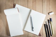 Top view of working object : gray pencil and many black pen near white notebook on wooden table. Gray pencil and many black pen near white notebook on wooden Royalty Free Stock Photo