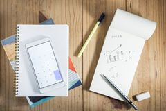 Top view of working object : gray pencil and white smartphone open calculator on white notebook on wooden table. Gray pencil and white smartphone open Royalty Free Stock Image