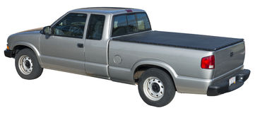 Gray Pick Up Truck, Tonneau Cover Isolated. Gray Chevy S10 pickup truck with a tonneau cover over the bed. The pick up has an extended cab. Isolated on white stock images