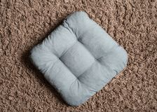 Gray pillow on the brown carpet. Background stock photo