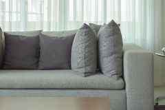 Gray pillows on beige color sofa with sheer in background Royalty Free Stock Photo