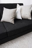 Gray pillows laying on a black sofa Stock Photo