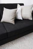 Gray pillows laying on a black sofa Stock Photo