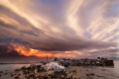 Gray Pink Blue White Clouds Above Rocky Shore Stock Image