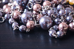 Gray and pink pearl  necklace on a dark background with reflecti. Gray and pink pearl necklace on a dark background with reflection Royalty Free Stock Images