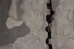 Gray plastered wall divided by wide crack. Rough texture Royalty Free Stock Photo