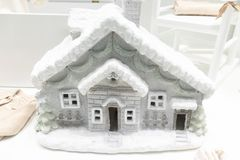 Gray plastic winter decorative house with snowy roof in the store front royalty free stock images
